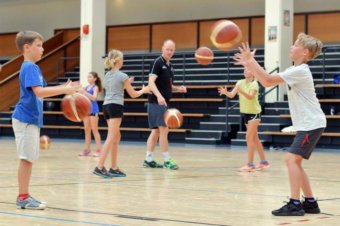 Trainer des TV Heppenheim bringen Ferienspielkindern die Grundlagen von Basketball bei